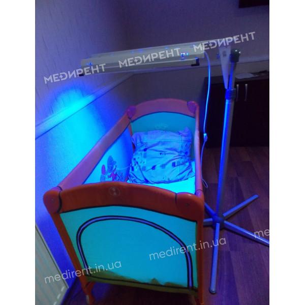 Лампа для фототерапии установлена сбоку кроватки новорожденного для лечения желтухи