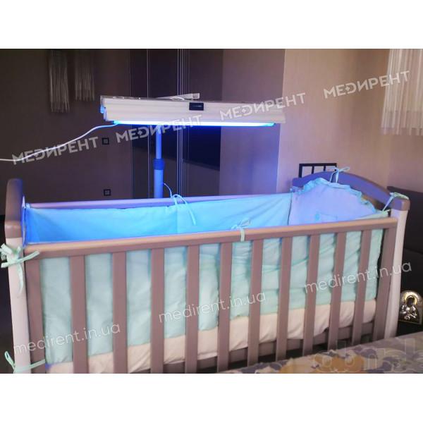 Сеанс фототерапии с помощью фотолампы над кроваткой новорожденного