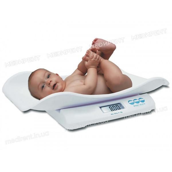 Младенец на весах с электронным табло для взвешивания